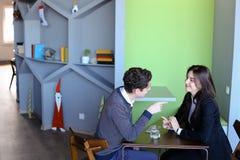 Los hombres jovenes y las mujeres comunican y comparten los secretos, asistiendo adentro imagen de archivo libre de regalías