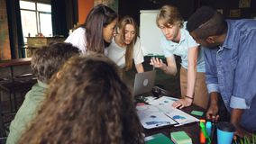 Los hombres jovenes y las mujeres están trabajando con las cartas y los gráficos alrededor de la tabla, equipo están hablando dis almacen de video