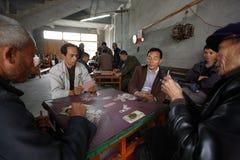 Los hombres juegan a un juego chino de tarjeta en el pueblo de Fuli. CIUDAD DE YANGSHUO, GU Foto de archivo