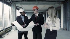 Los hombres, la mujer en traje y el casco discuten el modelo, comunican con el comprador Constructor del ingeniero jefe almacen de video