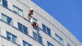 Los hombres limpian las ventanas de un edificio imágenes de archivo libres de regalías