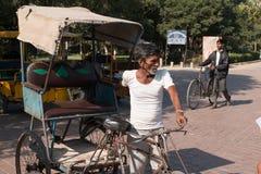 Los hombres no identificados conducen el pedicab delante del indicador occidental de Taj Mahal el monumento del amor Imágenes de archivo libres de regalías