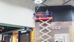 Los hombres pintan negro de la fachada de la tienda de zapatos encendido scissor el timelapse de la elevación almacen de metraje de vídeo