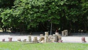 Los hombres ponen las tejas de pavimentación multicoloras decorativas en un parque del ` s de los niños Reparación de la acera Tr metrajes