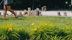 Los hombres ponen las tejas de pavimentación multicoloras decorativas en un parque del ` s de los niños Reparación de la acera Tr almacen de video