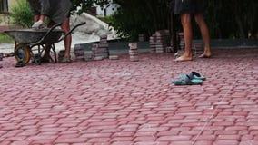 Los hombres ponen las tejas de pavimentación multicoloras decorativas en un parque del ` s de los niños Reparación de la acera Tr almacen de metraje de vídeo