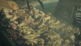 Los hombres que cocinan la carne asan en la parrilla de la barbacoa al aire libre Ciérrese encima de la carne de proceso de la ba metrajes
