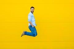 Los hombres que saltan en fondo amarillo imagen de archivo