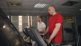Los hombres realizan ejercicio en una rueda de ardilla en el gimnasio almacen de metraje de vídeo