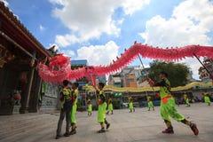 Los hombres realizan el baile del dragón para practicar se preparan por Año Nuevo lunar en una pagoda Fotos de archivo