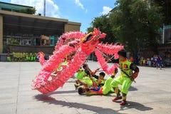 Los hombres realizan el baile del dragón para practicar se preparan por Año Nuevo lunar en una pagoda Imagen de archivo