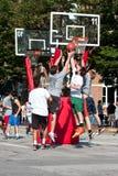 Los hombres saltan mientras que luchan para la bola en el torneo del baloncesto de la calle Fotografía de archivo libre de regalías