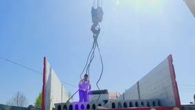 Los hombres se aferran un bloque de cemento en el gancho de una grúa del camión almacen de video