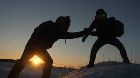 Los hombres se ayudan a conquistar la cumbre de la alta monta?a nevosa llevando a cabo las manos y estir?ndose para rematar en almacen de metraje de vídeo