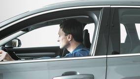 Los hombres se sientan en el nuevo coche almacen de metraje de vídeo