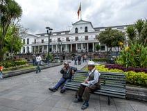 Los hombres se sientan en un banco de parque en cuadrado de la independencia en Quito en Ecuador Imagen de archivo