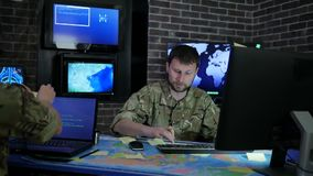 Los hombres serios del oficial en camuflaje uniforman en centro de control de sistema, trabajando para el ordenador portátil, inf almacen de video