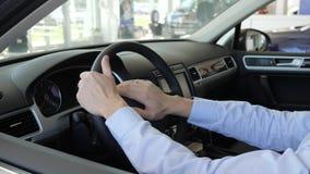 Los hombres sostienen el volante dentro del coche, manos del ` s del hombre en el timón, afortunado metrajes