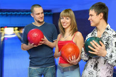 Los hombres sostienen las bolas para el bowling y la mirada en la muchacha Foto de archivo libre de regalías