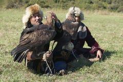 Los hombres sostienen las águilas de oro (chrysaetos) de Aquila, Almaty, Kazajistán Fotografía de archivo
