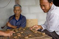 Los hombres tailandeses están jugando al ajedrez chino - XiangQi Fotografía de archivo libre de regalías