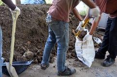Los hombres tailandeses que cavan el suelo para hacen el jardín Imágenes de archivo libres de regalías