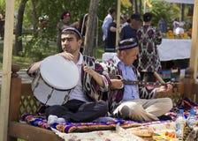Los hombres tocan los instrumentos musicales nacionales imagen de archivo