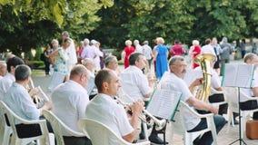 Los hombres tocan los instrumentos musicales en la orquesta en el parque el día de verano almacen de metraje de vídeo