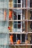 Los hombres trabajan en el andamio de edificios Fotografía de archivo libre de regalías