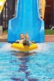 Los hombres van abajo del tobogán acuático a la piscina en parque de la aguamarina Happ Imagen de archivo
