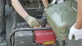 Los hombres vierten la gasolina del bote en el generador almacen de metraje de vídeo