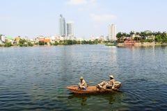 Los hombres vietnamitas en un barco limpian el lago del oeste Imagen de archivo libre de regalías