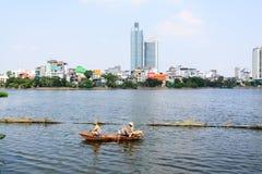 Los hombres vietnamitas en un barco limpian el lago del oeste Imagenes de archivo