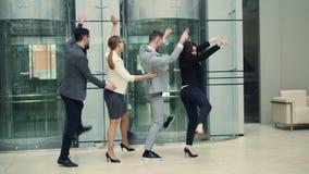 Los hombres y los empresarios de risa de las mujeres se están divirtiendo en el baile de las fiestas en la oficina en pasillo jun metrajes
