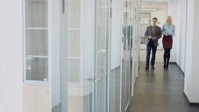 Los hombres y las mujeres de negocios caminan a lo largo del pasillo de la oficina y hablan metrajes