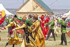 Los hombres y las mujeres en trajes nacionales bailan danzas populares tradicionales Foto de archivo libre de regalías