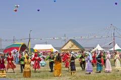 Los hombres y las mujeres en trajes nacionales bailan danzas populares tradicionales Imagen de archivo