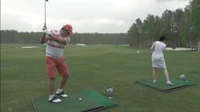 Los hombres y los jugadores de golf de la mujer están disfrutando del juego en el campo de golf juntos Pares en verde del golf Ho almacen de video