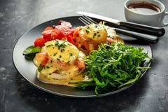 Los huevos Benedicto en el mollete inglés con el salmón ahumado, el cohete salvaje y el hollandaise sauce en una placa negra Fotos de archivo