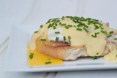 Los huevos Benedicto tostaron los huevos escalfados y holla del jamón de los molletes ingleses Imagenes de archivo