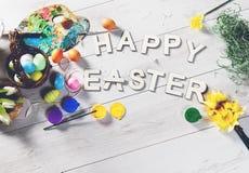 Los huevos coloreados y otras decoraciones en una tabla de madera blanca con PASCUA FELIZ firman Foto de archivo libre de regalías