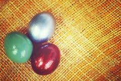 Los huevos coloridos en la armadura de bambú cubren el fondo, imagen del estilo del vintage Fotos de archivo