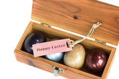 Los huevos coloridos en la caja de madera en el fondo blanco con pascua feliz marcan con etiqueta Fotografía de archivo