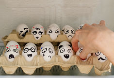 Los huevos con emociones pintadas en el refrigerador, una mano femenina toman una de ellas Fotos de archivo libres de regalías