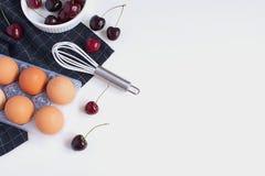 Los huevos crudos baten cerezas maduras del ramekin blanco y de la servilleta a cuadros imagen de archivo