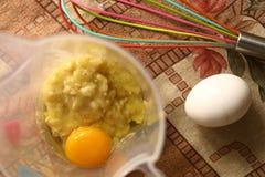 Los huevos crudos con el plátano trituraron cocinar la torta Imágenes de archivo libres de regalías