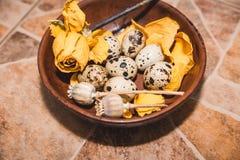 Los huevos de codornices con la flor amarilla están en el suelo de baldosas Fotografía de archivo