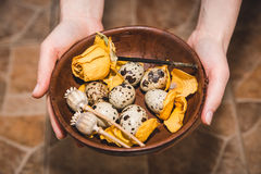 Los huevos de codornices con la flor amarilla están en la tabla marrón en el fema Imagen de archivo libre de regalías