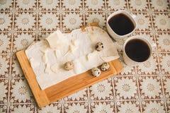 Los huevos de codornices con queso y lavash están en la tabla de cortar el pan de madera a Foto de archivo libre de regalías