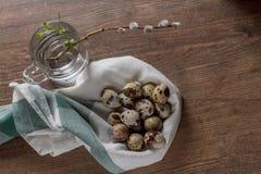 Los huevos de codornices en una tabla y un sauce de madera viejos ramifican Fotos de archivo